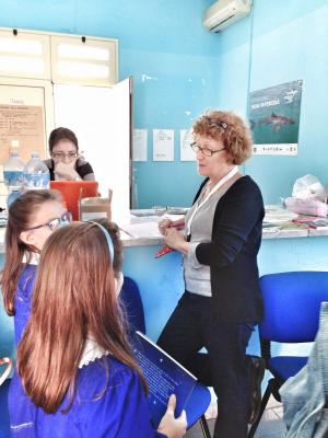 Mariella spiega a due bimbe, all'uscita da scuola, il funzionamento della biblioteca