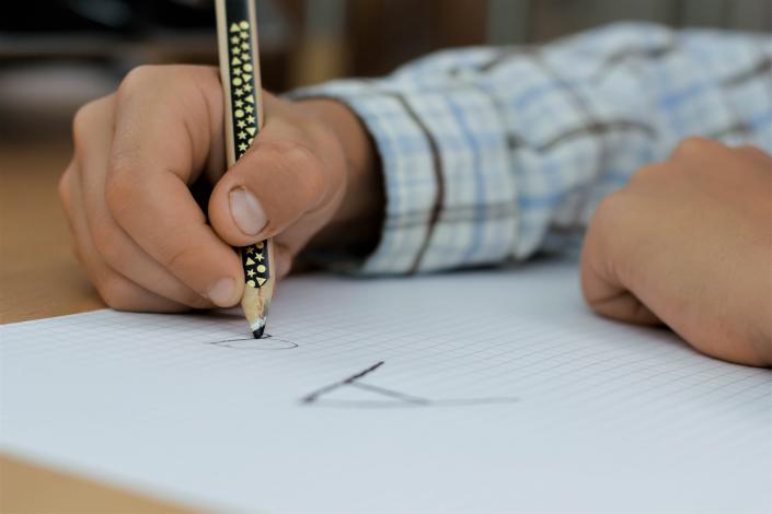 ragazzo che sta scrivendo con la penna