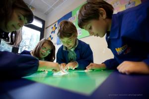 Gli alunni impegnati durante il lavoro di gruppo sullo SMART Table. Foto di Giuseppe Moscato, fonte immagine: http://bricks.maieutiche.economia.unitn.it